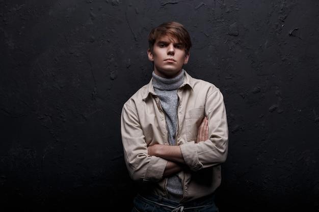 Junger stilvoller mann mit einer modischen frisur in einer jacke im grauen pullovergolf in der kühlen blauen jeans, die die kamera in einem studio nahe der wand aufwirft und betrachtet. amerikanischer süßer kerl. moderne herrenmode.