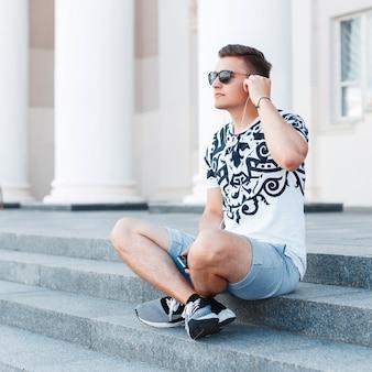 Junger stilvoller mann mit sonnenbrille, die auf der treppe sitzt und musik hört.