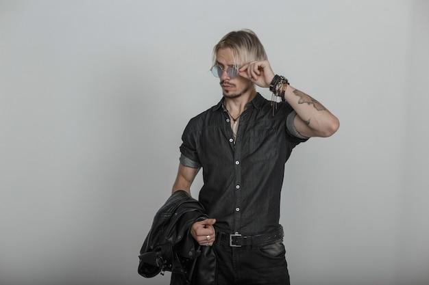 Junger stilvoller mann steht fest an vintage runden blauen gläsern. blonder kerl in schwarzer jeanskleidung mit einer jacke, die drinnen nahe der wand aufwirft. modische herrenbekleidung und accessoires.