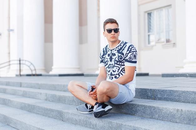 Junger stilvoller trendiger mann in der sonnenbrille, die auf der treppe sitzt.