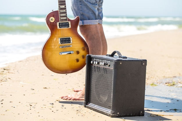 Junger stilvoller typ am strand mit musikinstrumenten, dem konzept von musik und entspannung