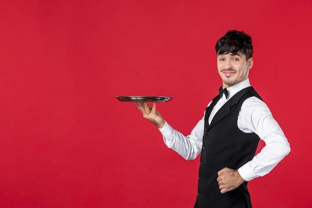 Junger stolzer, selbstbewusster kellner in uniform, der schmetterling am hals hält, der tablett auf isoliertem rotem hintergrund hält