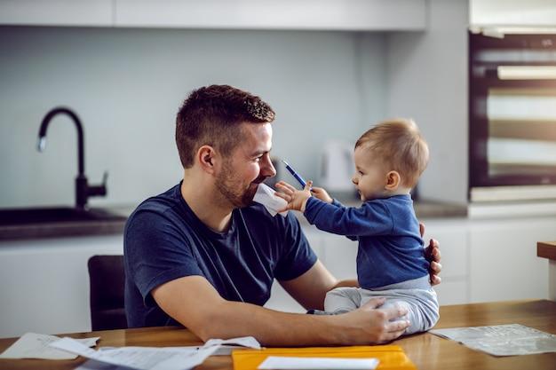 Junger stolzer vater, der am esstisch sitzt, rechnung im mund hat und seinen sohn hält. das kleinkind sitzt auf dem tisch und hilft seinem vater, die rechnung auszufüllen.