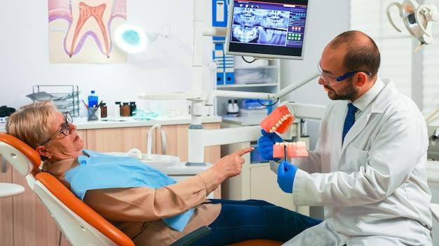 Junger stomatologe, der das verfahren des älteren patienten unter verwendung des modells der zahnzähne erklärt. arzt, der eine probe des menschlichen kiefers hält, die informationen zur erhaltung gesunder zähne, digitales röntgen im hintergrund