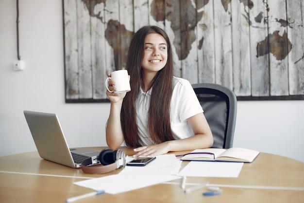 Junger student, der am tisch sitzt und den laptop benutzt