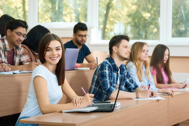 Junger student, der die kamera sitzt in der universität betrachtet.