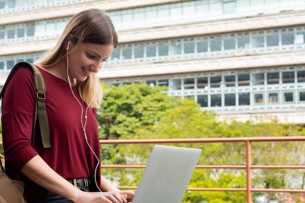 Junger student, der draußen laptop verwendet.