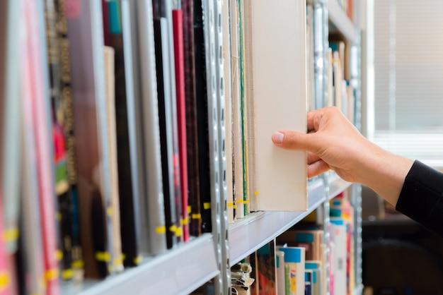Junger student, der ein buch aus dem regal in der bibliothek auswählt.