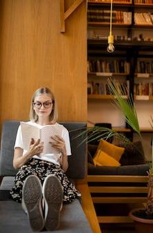 Junger student, der ein buch in der bibliothek liest