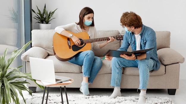 Junger student, der gitarre lernt und medizinische maske trägt