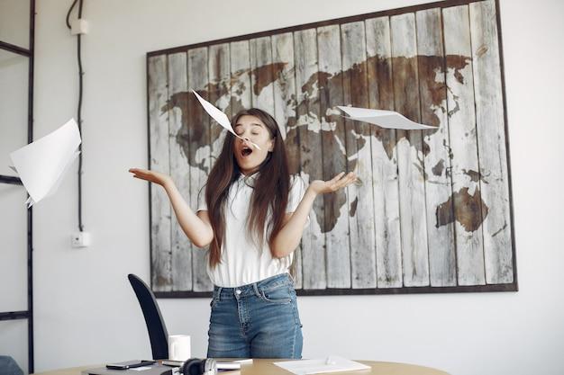 Junger student, der im büro steht und oben die dokumente wirft