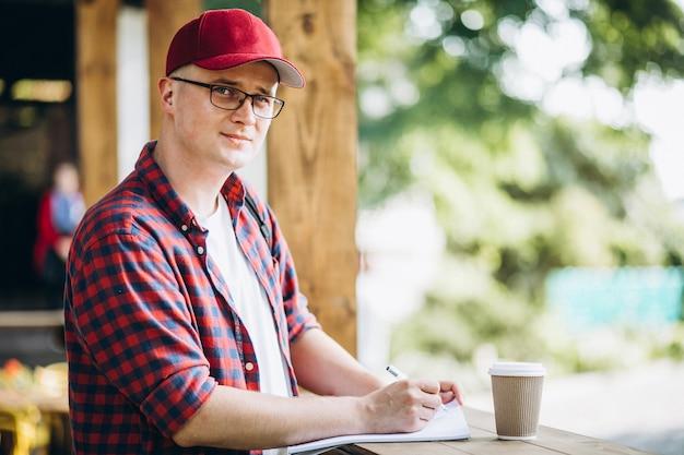 Junger student, der in einem café im park arbeitet