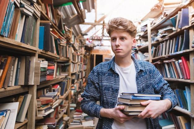 Junger student, der in einer bibliothek mit büchern in seinen händen geht und nach literatur sucht.