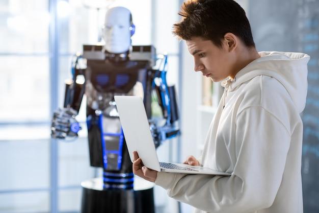 Junger student, der laptopanzeige beim arbeiten mit automatisierungsroboter im labor oder im klassenzimmer des zeitgenössischen instituts betrachtet