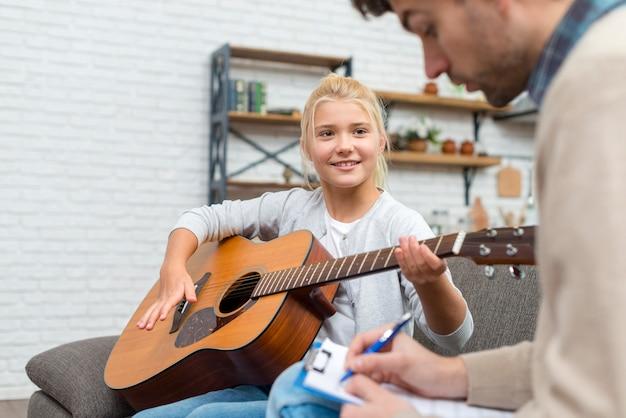 Junger student, der lernt, wie man gitarre spielt