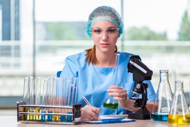 Junger student, der mit chemischen lösungen im labor arbeitet