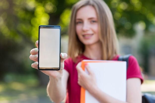 Junger student, der smartphoneschablone zeigt