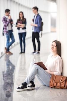 Junger student der weiblichen schönheit, der ein buch liest.