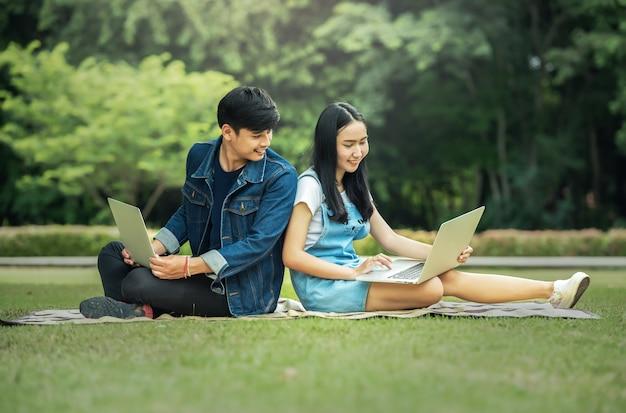 Junger student, der zusammen laptop im park verwendet