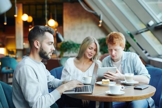 Junger student in der freizeitkleidung, die am tisch im café vor laptop und vernetzung auf hintergrund seiner freunde unter verwendung des touchpads sitzt