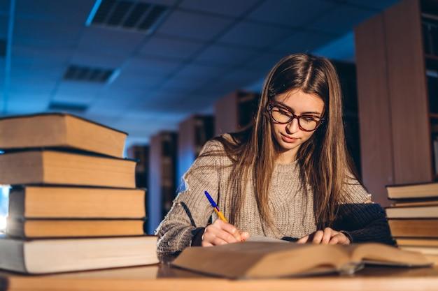 Junger student in gläsern, die sich auf die prüfung vorbereiten. mädchen am abend sitzt an einem tisch in der bibliothek mit einem stapel bücher