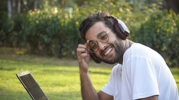 Junger student mit dem lächelnden laptop, der kopfhörer während des videoanrufs trägt - mann mit laptop