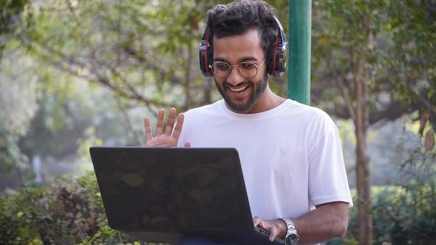 Junger student mit laptop auf videoanruf, der hallo mann mit laptop sagt