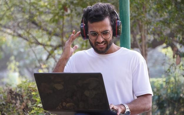Junger student mit laptop - netzwerkproblem während videoanrufmann mit laptop