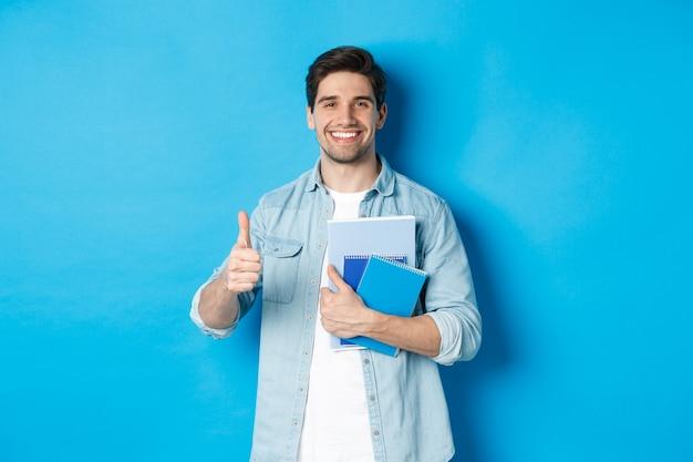 Junger student mit notizbüchern, daumen hochzustimmend, zufrieden lächelnd, blauer studiohintergrund