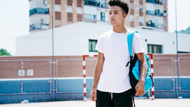 Junger student mit rucksack auf dem schulhof