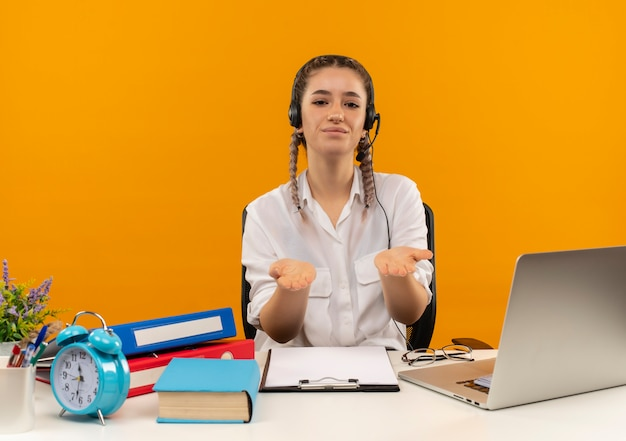 Junger student mit zöpfen in weißem hemd und kopfhörern, die studieren