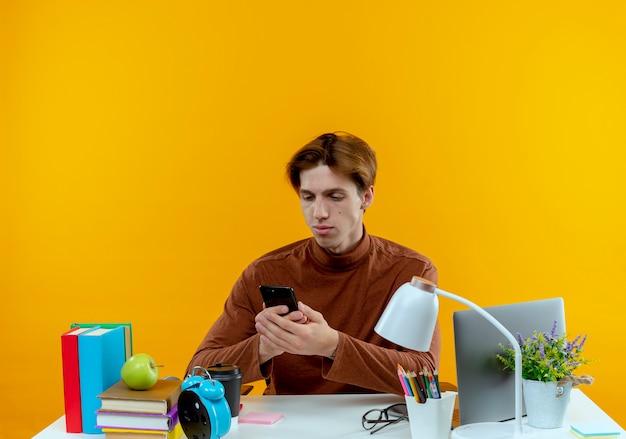 Junger studentenjunge, der am schreibtisch mit schulwerkzeugen sitzt und telefon lokalisiert auf gelber wand hält