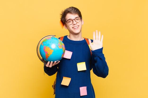 Junger studentenjunge, der glücklich und fröhlich lächelt, mit der hand winkt, sie begrüßt und begrüßt oder sich verabschiedet