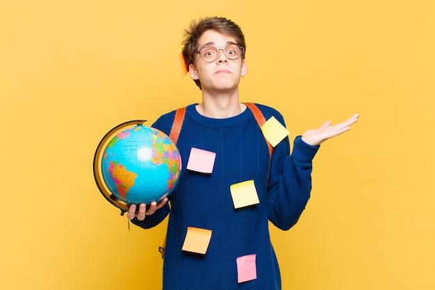 Junger studentenjunge, der sich verwirrt und verwirrt fühlt, zweifelt, gewichtet oder verschiedene optionen mit lustigem ausdruck wählt