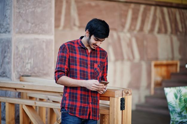 Junger studentenmann an rotem kariertem hemd und an jeans stellte stadt mit handy an händen auf