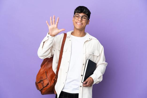 Junger studentenmann auf isoliertem purpur, der fünf mit den fingern zählt