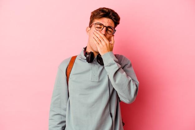 Junger studentenmann auf rosa gähnen zeigt eine müde geste, die mund mit hand bedeckt.