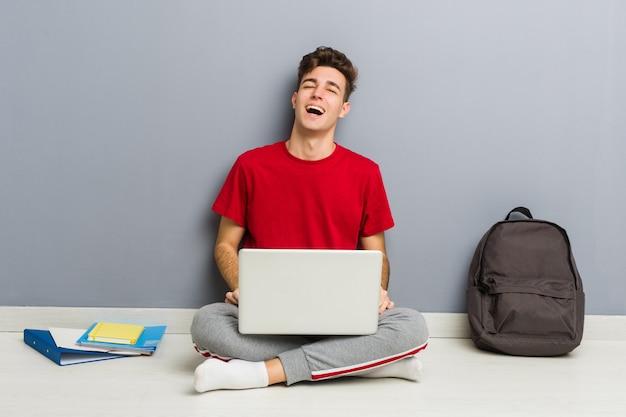 Junger studentenmann, der auf seinem hausboden hält einen laptop sitzt