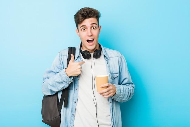 Junger studentenmann, der einen kaffee zum mitnehmen in der hand hält, zeigte überrascht auf sich selbst und lächelte breit