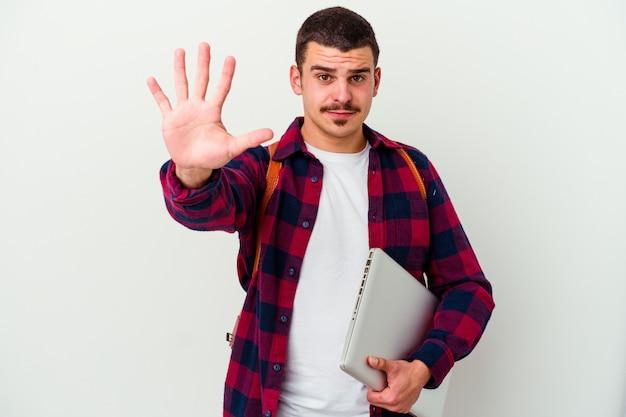 Junger studentenmann, der einen laptop lokalisiert auf weißer wand hält, der fröhlich zeigt nummer fünf mit den fingern zeigt