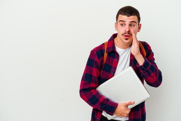 Junger studentenmann, der einen laptop lokalisiert auf weißer wand hält, sagt eine geheime heiße bremsnachricht und schaut zur seite