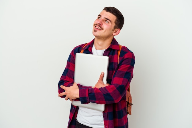 Junger studentenmann, der einen laptop lokalisiert auf weißer wand hält und davon träumt, ziele und zwecke zu erreichen