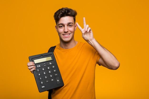 Junger studentenmann, der einen taschenrechner seitlich schaut mit zweifelhaftem und skeptischem ausdruck hält.