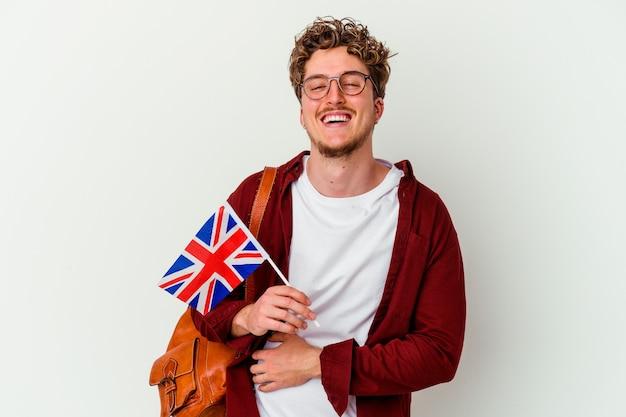 Junger studentenmann, der englisch isoliert auf weißer wand lacht und spaß hat