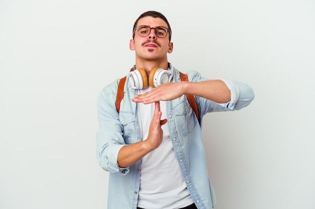 Junger studentenmann, der musik lokalisiert auf weißer wand hört, die eine zeitüberschreitungsgeste zeigt