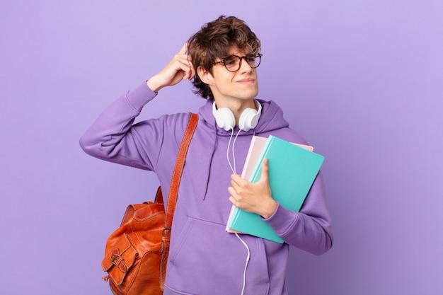 Junger studentenmann, der sich verwirrt und verwirrt fühlt und sich am kopf kratzt
