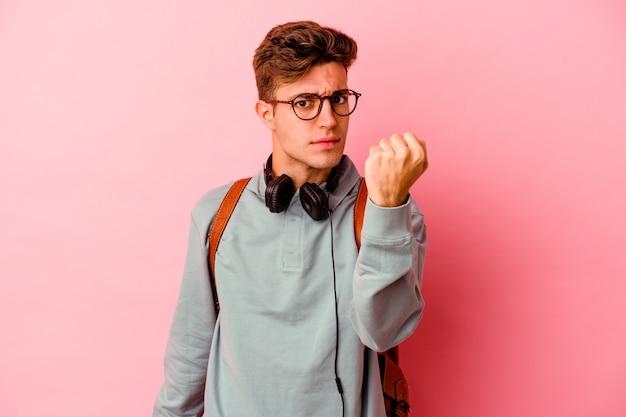 Junger studentenmann einzeln auf rosafarbenem hintergrund, der faust zur kamera zeigt, aggressiver gesichtsausdruck.