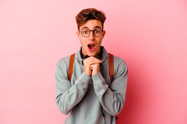 Junger studentenmann einzeln auf rosafarbenem hintergrund, der um glück betet, erstaunt und den mund öffnet, der nach vorne schaut.