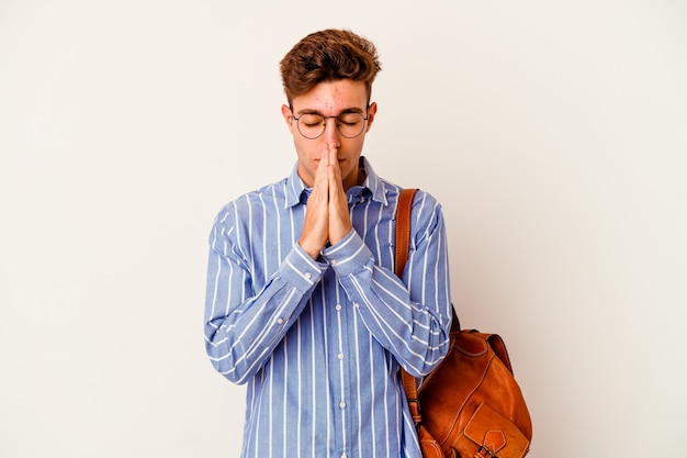 Junger studentenmann lokalisiert auf weißem hintergrund, der hände im gebet nahe mund hält, fühlt sich zuversichtlich.