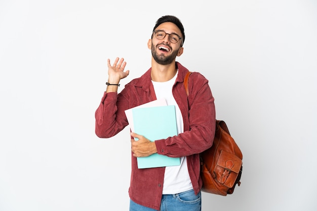 Junger studentenmann lokalisiert auf weißem hintergrund, der mit der hand mit glücklichem ausdruck grüßt